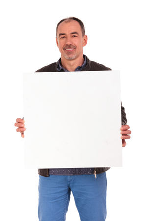 billboards: handsome mature man in leather jacket posing while holding a white board in isolated studio background and looking at the camera Stock Photo