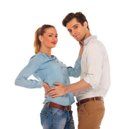 près portrait d'un couple mignon embrasser en blanc isolé fond studio tout en regardant la caméra
