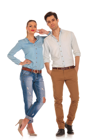 legs crossed: attractive caucasian couple posing in white isolated studio background looking at the camera. man has both hands in pockets and woman rests her arm on his sholder with legs crossed Stock Photo