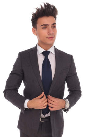 cerrando negocio: vista lateral de un joven hombre de negocios cerrando o abriendo su traje mientras mira a la c�mara sobre fondo blanco