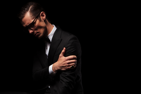 dark side: side view of classy smart man in black suit posing looking down while touching his arm in dark studio background