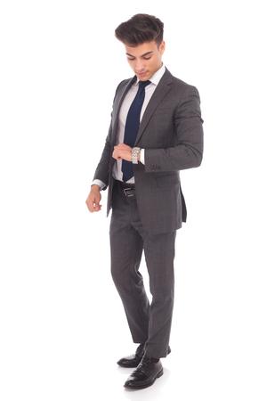 cuerpo hombre: foto de cuerpo entero de un joven hombre de negocios que controla el tiempo en su reloj en el fondo blanco del estudio