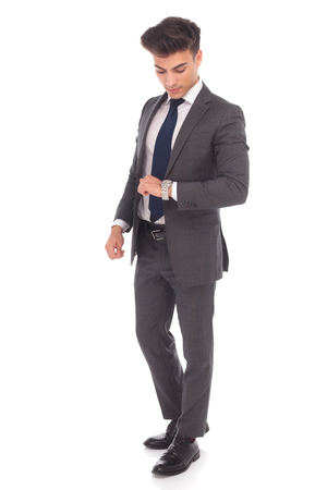 checking time: full body picture of a young business man checking time on his watch on white studio background