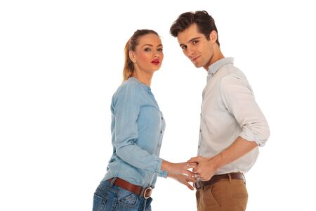 facing to camera: cute couple posing holding hands and facing each other while looking at the camera in isolated studio background Stock Photo