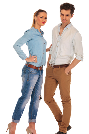 boyfriend: attractive boyfriend and girlfriend posing in white isolated studio background while looking at the camera. the man has both hands in pockets and woman is touching his arm