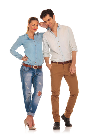 shoulders: cute couple posing in white isolated studio background. woman with legs crossed looking at the camera while resting arm on his shoulder. man with hand in pocket looks down Stock Photo