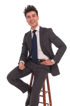 ooking: laughing young business man sitting on a chair and looks to side on white background