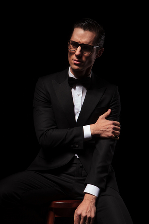 classy man in black suit wearing glasses posing in dark studio background touching his arm and looking away