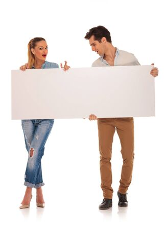 legs crossed: handsome couple posing in isolated studio background holding a blank white sign. man is looking away while woman is looking at the camera with legs crossed