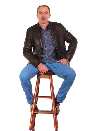 man sit: elegant mature man in leather jacket posing on stool with legs open while looking at the camera in isolated studio background