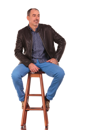 legs open: elegant mature man in leather jacket posing seated on stool with legs open while looking away from the camera in isolated studio background Stock Photo