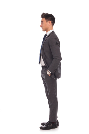 casual business man: side view of a young business man standing in line with hands in his pockets Stock Photo