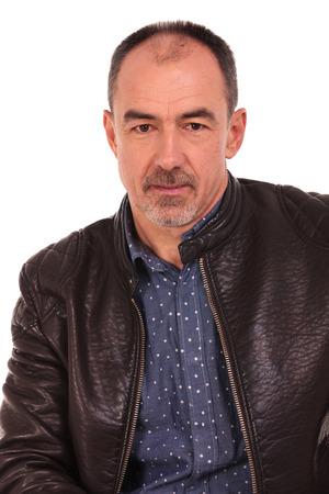 portret van volwassen, kaal, casual man in leater jas poseren in geïsoleerde studio achtergrond te kijken naar de camera