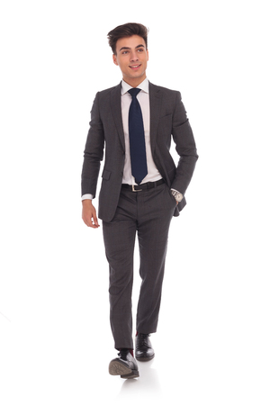 young businessman: relaxed young business man is walking with one hand in his pocket and looks to his side on white background