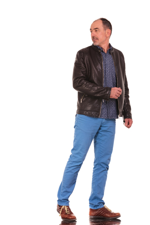 turn away: mature elegant man in leather jacket walking and turning in isolated studio background while looking away from the camera