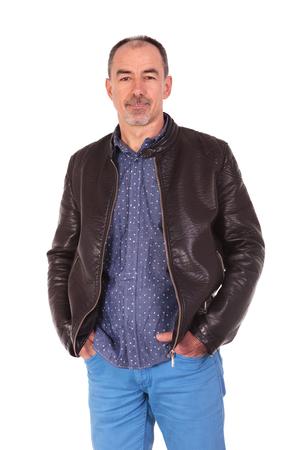 cuerpo hombre: Retrato de la cara de hombre confía en la chaqueta de cuero que presenta con las dos manos en los bolsillos mientras mira a la cámara aislada en el fondo del estudio Foto de archivo