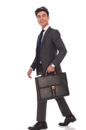 cuerpo hombre: vista lateral de un hombre de negocios de pie con maletín mirando hacia arriba y que ríe en el fondo blanco
