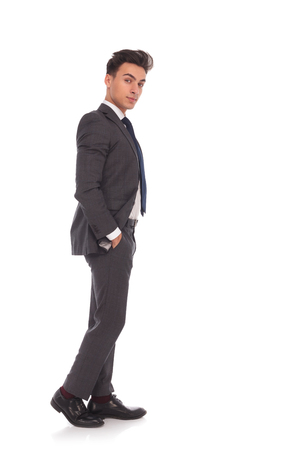 side view of a young relaxed business man standing with hands in pockets on white studio background, looking at the camera