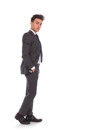vue de côté d'un jeune homme d'affaires décontractée debout avec les mains dans les poches sur fond blanc studio, en regardant la caméra