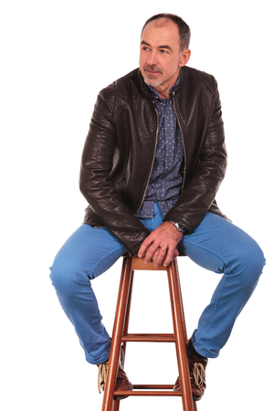 legs open: mature man in leather jacket posing seated on chair with legs open while looking away from the camera in isolated studio background Stock Photo