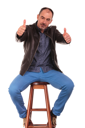 legs wide open: mature man posing seated with legs wide open in isolated studio background while showing thumbs up with both hands