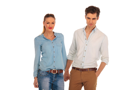 women in jeans: beautiful couple posing in white isolated studio background holding hands. the man is looking at the camera with one hand in pocket. Stock Photo