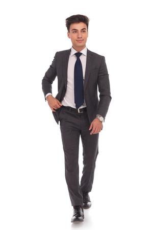caminando: foto de cuerpo entero de un joven hombre de negocios de pie y mirando a la cámara sobre fondo blanco estudio Foto de archivo