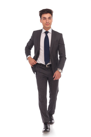 walking: full body picture of a young business man walking and looking away from the camera on white studio background