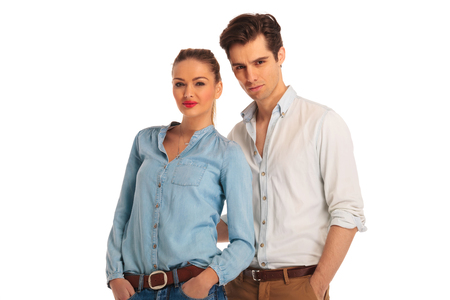 women in jeans: close portrait of young couple posing with hands in pockets in white isolated studio background looking at the camera Stock Photo
