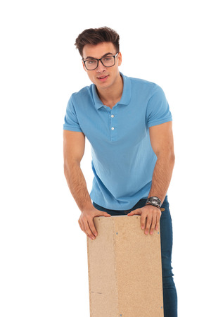 resting: portrait of handsome man resting with hands on wooden box while looking at the camera in isolated studio background Stock Photo