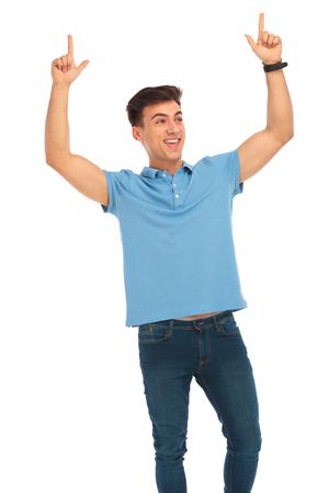 joven de camisa azul celebrando con ambas manos levantadas, que apunta hacia arriba mientras se mira lejos en el fondo del estudio aislado Foto de archivo