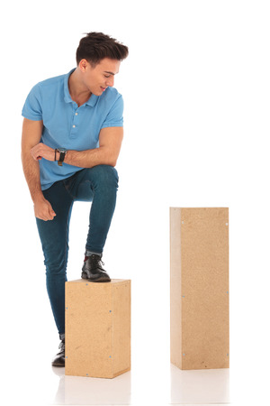 isolated man: handsome boy with a leg on a box looking down at something on a wooden box in isolated studio background
