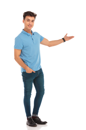 stylish man in blue shirt presenting with hand in pocket while looking at the camera in isolated studio background
