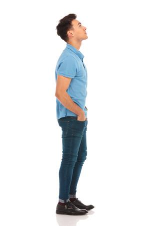 personas mirando: Retrato de la cara del hombre joven en camisa azul mirando hacia arriba con las manos en los bolsillos mientras que presenta en fondo del estudio aislado Foto de archivo