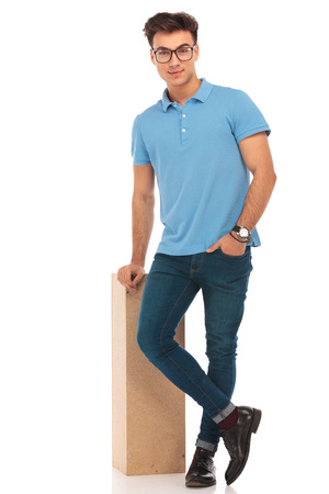 legs crossed: portrait on handsome boy standing with legs crossed and hand in pocket while resting on box looking at the camera in isolated studio background Stock Photo
