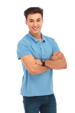 portrait of smiling young man in blue shirt posing with arms crossed while looking at the camera in isolated studio background