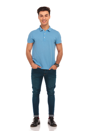portrait of stylish young man in blue shirt posing with hands in pockets looking at the camera in isolated studio background Foto de archivo