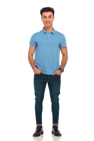 cuerpo entero: retrato de hombre joven con estilo en camisa azul que presenta con las manos en los bolsillos mirando a la cámara aislada en el fondo del estudio