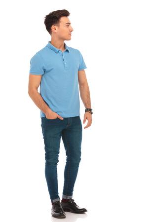 Portret van knappe man in blauw shirt poseren met een hand in de zak terwijl kijkend weg van de camera in geïsoleerde studio achtergrond Stockfoto