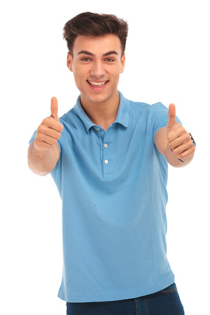 isolated man: young man in blue shirt smiling and showing thumbs up sign while looking at the camera in isolated studio background Stock Photo
