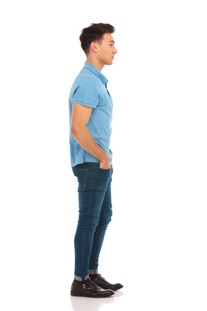 side portrait of young man in blue shirt looking ahead with hands in pockets in isolated studio background while posing for the camera
