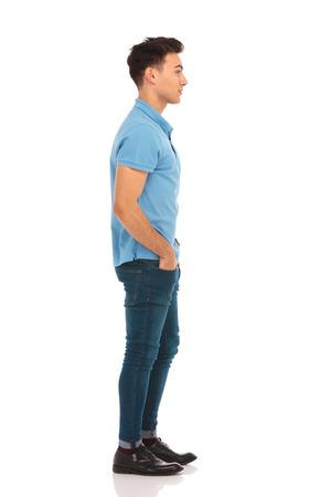 kant portret van de jonge man in blauw shirt vooruit te kijken met de handen in de zakken in geïsoleerde studio achtergrond terwijl poseren voor de camera
