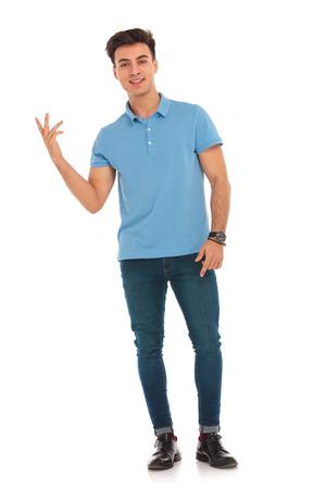 分離のスタジオの背景にカメラを見ながら指を指している青いシャツの男性の肖像画 写真素材