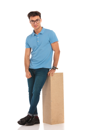 man sit: portrait of happy man with legs crossed wearing glasses, resting on a wooden box while looking at the camera in isolated studio background