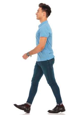 side portrait of young man in blue shirt walking in isolated studio background, looking away from the camera