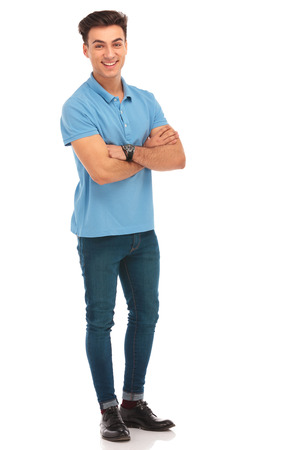 happy hipster in blue shirt posing with arms crossed in isolated studio background while looking at the camera