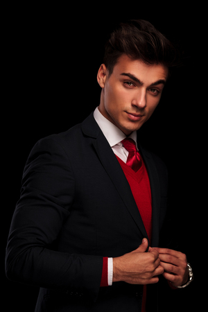 red  man: portrait of classy young man in suit, fixing his jacket while looking at the camera in dark studio background