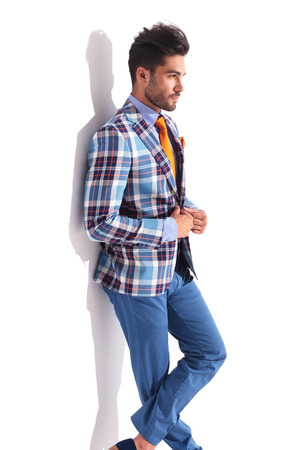 legs crossed: smart casual man standing with legs crossed in studio background while fixing his plaid jacket and looking away from the camera