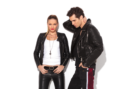 cute man: hot young couple in leather clothes, man with hands behind his neck and woman standing with hands on waist