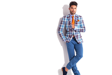 legs crossed: smart casual man with hand in pocket posing with hand in jacket and legs crossed while looking away from the camera in white studio background